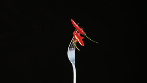 Fork With Three Chili Peppers on Black Background Footage