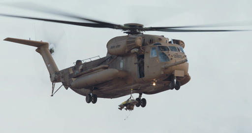 Sikorsky CH-53E Super Stallion hovering while a soldier is rescuing a wounded pe Live Action