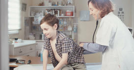 Doctor checking a young boy at the hospital Footage