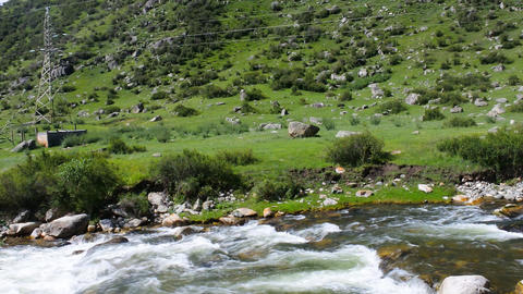 Hydropower. Mountain river in green valley and Line power Footage