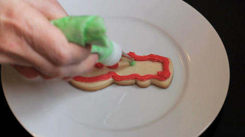 Decorating Snowman Shaped Christmas Cookie With Green Icing Stock Video Footage