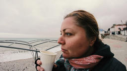 woman, that looks funny, drinking coffee on the cold beach Image