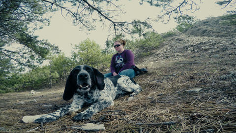 a woman with a dog resting in the forest Live Action