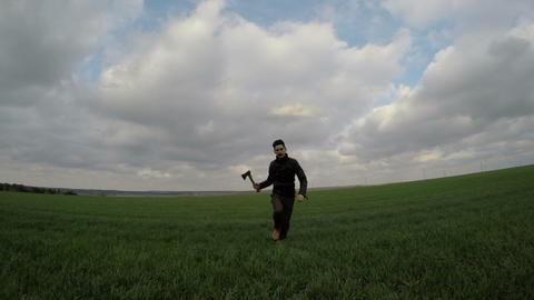 A man with an axe is running on field Footage