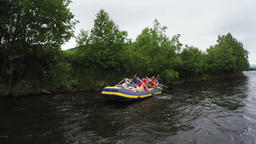 Rafting crew in rafting boat floats on river near coast with trees in forest Footage