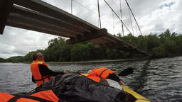 Rafting boat floats under dangerously low hanging suspension bridge over river Footage
