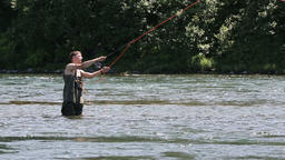 Fisherman angling on cold mountain river in summer season Footage