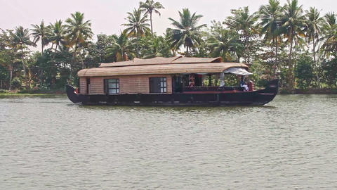 Close Floating House Sails along Wide River by Palms in Tropics Footage