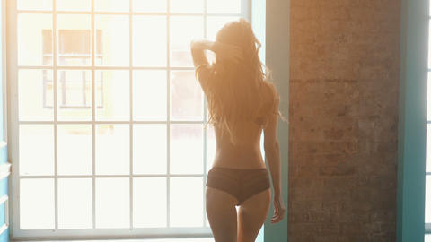 Sexy girl in black lingerie goes towards the window Footage