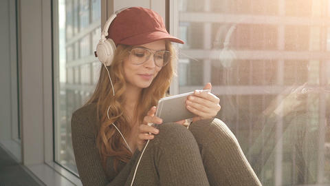 Cute girl sitting by window listening to music with headphones using mobile Footage