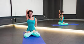 Woman doing yoga exercise at mirror 4k video. Girl sits lotus asana stretching Footage