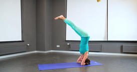 Woman doing yoga exercise 4k video. Girl head arms Headstand asana posture Footage