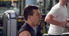 Man on cardio jogging training in gym 4k close-up video. Running on treadmill Footage