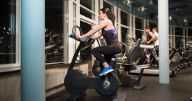 Woman cardio gym training 4k video. Fitness girl on stationary bicycle Footage