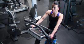 Woman cardio gym training 4k top video. Fitness girl on stationary bicycle Footage