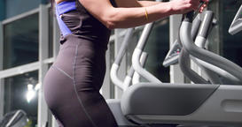 Woman cardio in gym 4k video. Fitness girl training elliptical exercise machine Footage