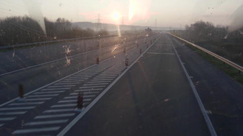 Car running on a highway in the early hours of the morning hours having the sun  Footage