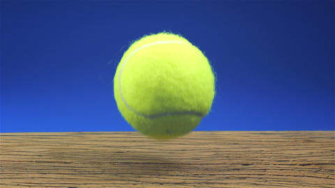 Tennisball bouncing on wood with blue background Live Action