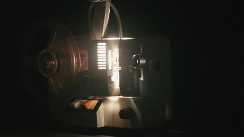 Old film camera projection is started by hand by a man then stops it after a whi Footage