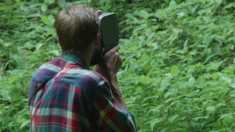 Tourist filming with an old camera on film the forest that is in front 12a Footage