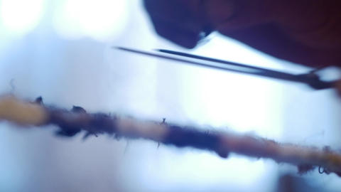 Woman cut with scissors attached to a node situated on a fabric to weaving loom  Footage