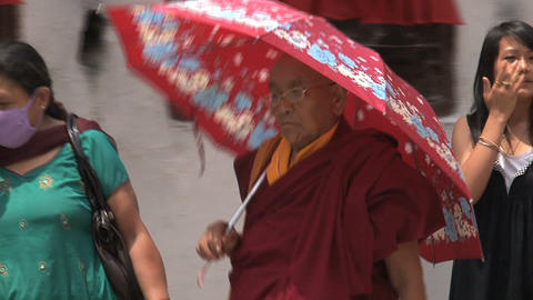 Older monk walking with an umbrella Footage
