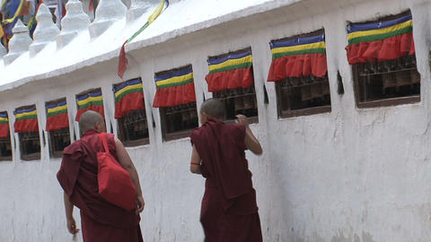 Monks walking while spinning the prayer wheels Stock Video Footage