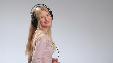 Happy smiling girl listening music in headphones Footage