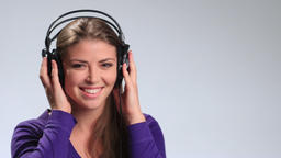 Cheerful pretty woman listening music in headphones Footage