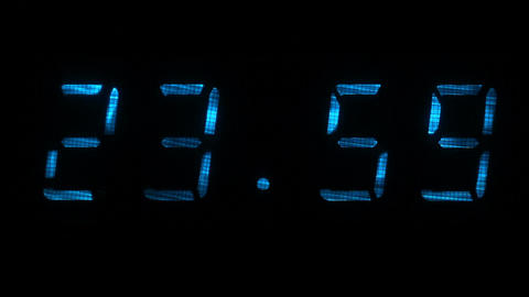 Digital clock shows the time of 23 hours 59 minutes to 00 hours 00 minutes Footage