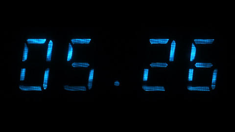Rapid adjustment of time on the digital clock display, blue digits on a black Footage