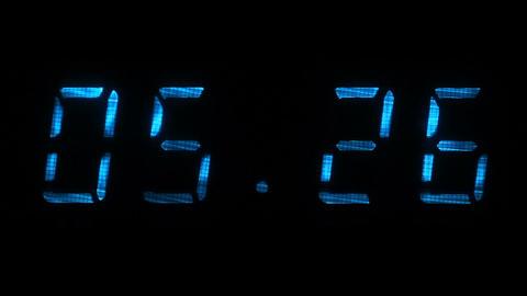 Rapid adjustment of time on the digital clock display, blue digits on a black Footage