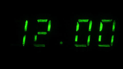 Digital clock shows the time of 11 hours 59 minutes to 12 hours 00 minutes Footage