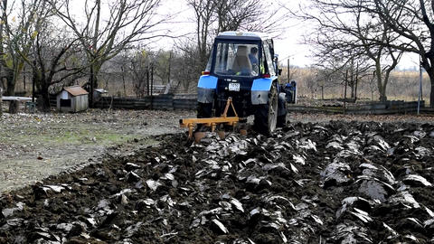 Tractor plowing the soil in the garden. Autumn plowing plow the garden Live Action