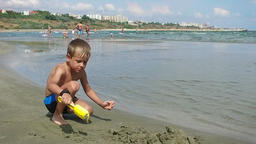 Little boy playing with sand, Constanta beach Romania, editorial Footage