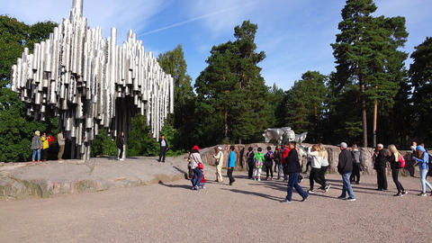 Tourists walk around ground square against Sibelius Monument, green park Footage