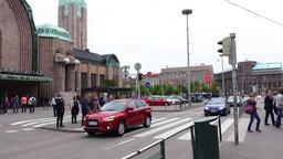 Helsinki central railway station, people cross road against main entrance Footage
