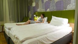 Young melancholic woman lie alone at double bed, look beside with drear mood Footage