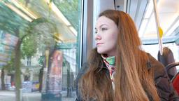 Woman travel in Helsinki tram, look out window, bright outdoors Footage
