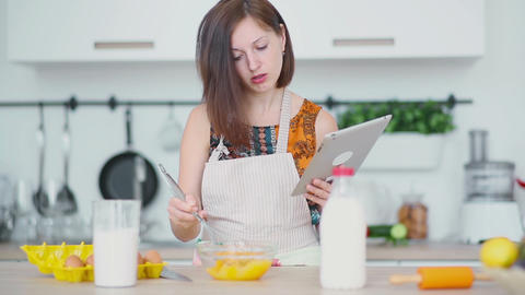 Woman is shaking up eggs and look on the pad Footage