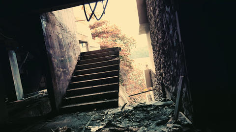 Shaky camera comes out of dark corridor and moves towards damaged staircase lead Footage