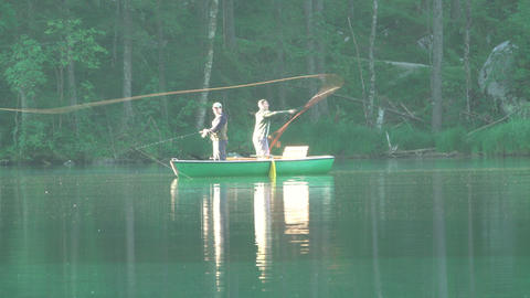 Two Fishermen in a Boat on Morning Forest Lake. Editorial Use Only Footage