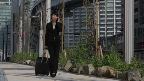 Asian Woman Talking On Mobile Phone Walking Near Office Building Footage