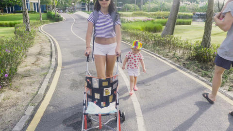 Woman in sunglasses is walking with baby and stroller Footage