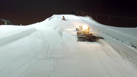 Aerial snowcat leveleing slope and climbs up to the top of the slope Filmmaterial
