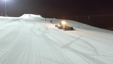 Aerial snowcat leveleing slope and climbs up to the top of the slope