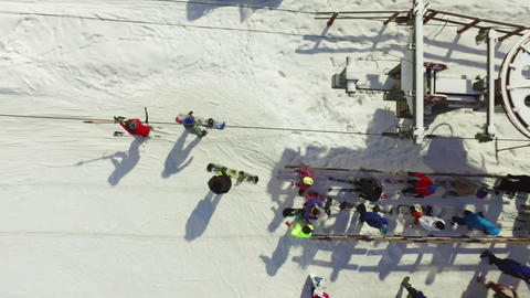 Aerial skiers and snowboarders go up the lift on the slope Footage