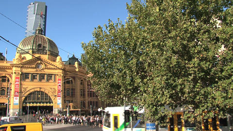 Busy street with people and trams around Flinders station Footage