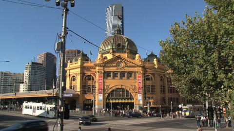 Trams and cars at a busy street around Flinders station Footage