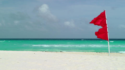 Red Flag Waving on Tropical Beach Stock Video Footage
